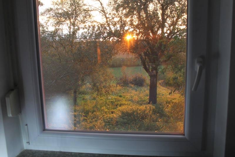Blick durch das Fenster vom Arbeitszimmer beim Sonnenuntergang.
