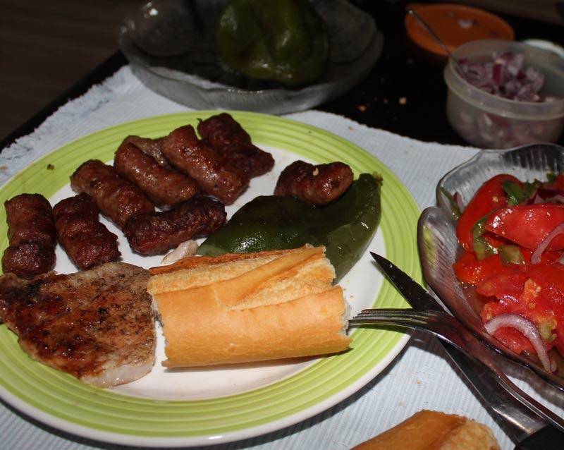 Teller mit fertig gegrillten Cevapcici, grünem, Paprika und Stück Grillfleisch.